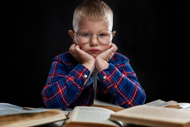 眼鏡をかけた悲しい太った少年が本をテーブルに座っています。教育と知識。閉じる。