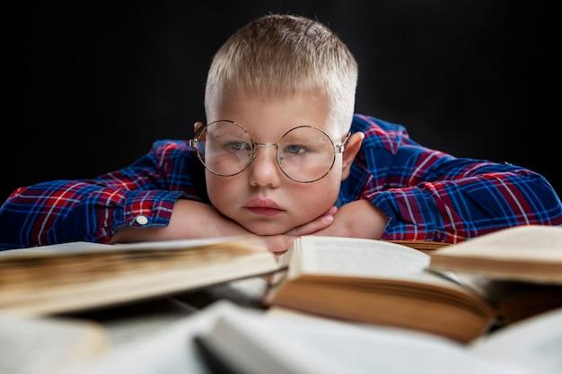 За столом сидит грустный толстяк в очках с книгами. образование и знания. крупный план.