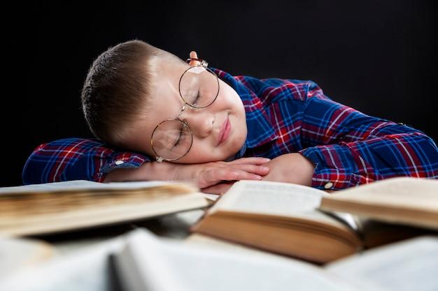眼鏡をかけた悲しい太った少年が本をテーブルで寝ています。教育と知識。閉じる。
