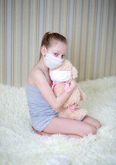 밝은 피부와 긴 머리를 가진 의료용 마스크의 슬픈 소녀가 마스크를 쓰고 프레임을 들여다 보는 테디 베어를 안아줍니다.