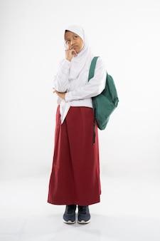 フード付きの小学校の制服を着た悲しい少女がランドセルを持って立っている