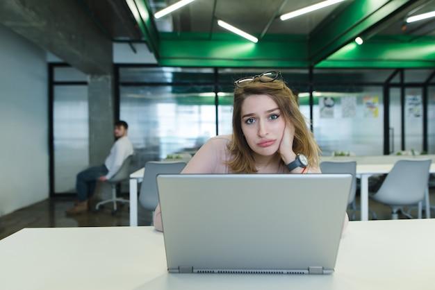 그녀의 손에 커피 한 잔 함께 슬픈 소녀 사무실에서 책상에 노트북을 사용합니다.