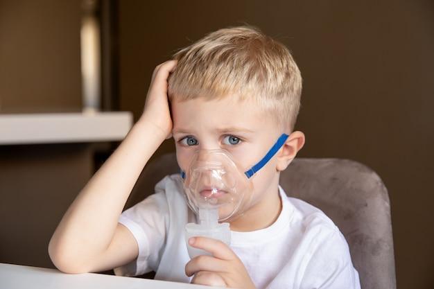 悲しい少年は自宅でネブライザーを使って吸入します彼は病気の喘息ですコンセプト健康