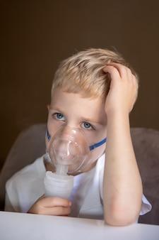 悲しい小さな男の子は自宅でネブライザーを吸入します彼は病気ですコンセプトヘルス