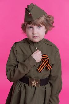 Грустная маленькая девочка в военной форме в праздничный день победы, 9 мая.