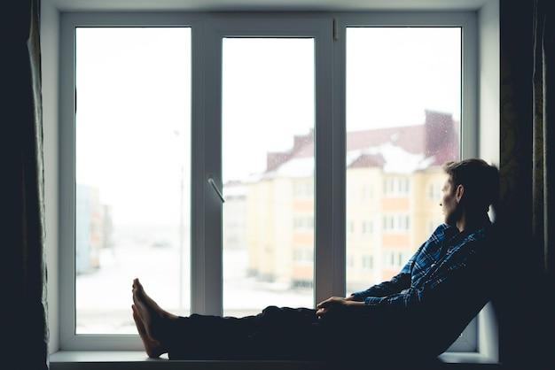 窓際の窓辺に座って遠く離れた屋外を見ている悲しい孤独な思いやりのある男のシルエット、