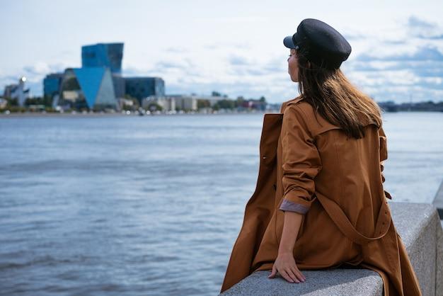 우울한 날에 재킷과 모자를 쓴 슬픈 외로운 여자가 강 제방에 앉아 거리를 들여다 본다.