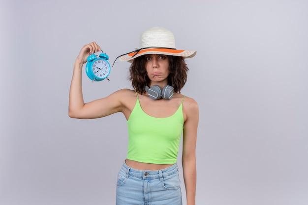 Грустная милая молодая женщина с короткими волосами в зеленом топе в шляпе от солнца держит синий будильник на белом фоне