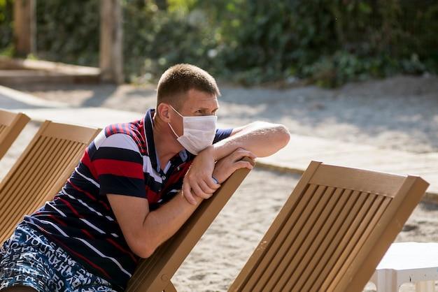悲しい男が、19インフルエンザの流行の最中に、ビーチで一人でマスクをかぶってデッキチェアに座っている