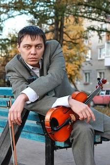 Грустный человек со скрипкой в руках сидит на скамейке