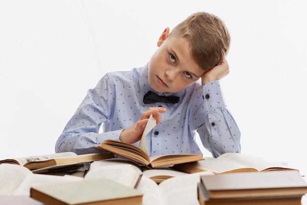 蝶ネクタイをした青いシャツを着た悲しい疲れた男子生徒が教科書の上に座っています。学校に戻る。白色の背景。