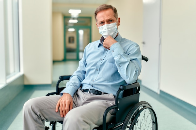 車椅子と保護用医療マスクを身に着けた悲しい、動揺した高齢の障害者の男性が、クリニックの廊下の真ん中に座って家族を待っています。
