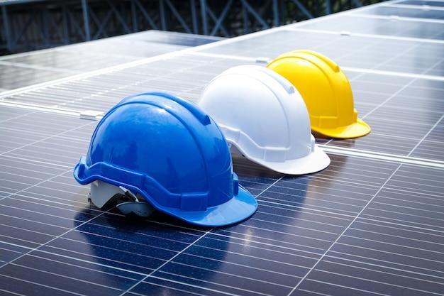 작업 중 머리 충돌을 방지하기위한 안전 헬멧, 파란색, 흰색, 노란색 기계공이 태양 광 패널에 배치됩니다. 에너지 기술의 개념, 작업. 복사 공간