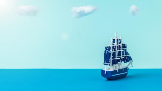 青い帆が岸から離れて航行している帆船。旅行と冒険の概念。インストール。