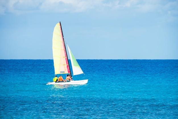 帆船は天気の良い日には青い海を渡って観光客を運びます。バラデロの美しいキューバのビーチでのセーリングボート。観光カタマラン。エコトランスポート