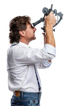 육분의를 가진 선원. 흰 셔츠와 청바지를 입은 성인 남자가 전문적인 장치로 거리를 측정합니다. 요트와 항해. 흰색 배경에 고립. 수직의.