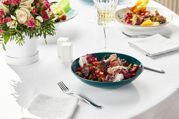 肝臓、野菜、ベリーのサラダ、花、ワイン、その他の軽食を添えたお祝いのテーブルで、子牛の肝臓をサラダに揚げました。