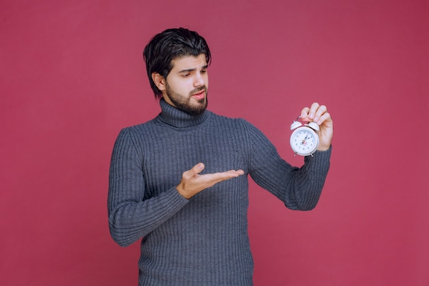 흰색 알람 시계를 들고 고객에게 홍보하는 세일즈맨.