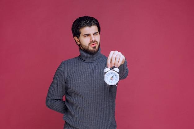 白い目覚まし時計を持って顧客に宣伝するセールスマン。