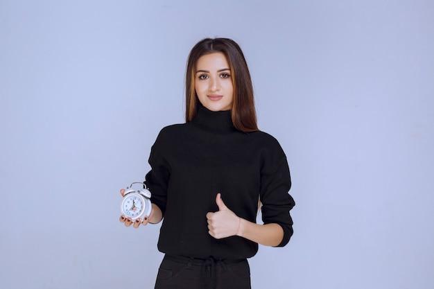 알람 시계를 들고 홍보하는 판매원.