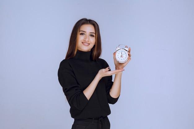 目覚まし時計を持って宣伝している店員。