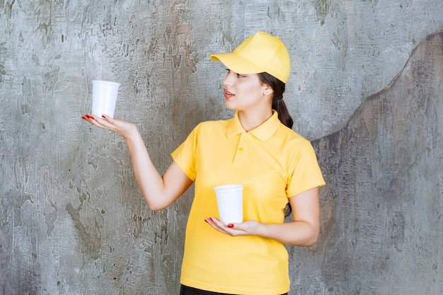 Продавщица в желтой форме держит два пластиковых стаканчика с напитком и дает один другому человеку