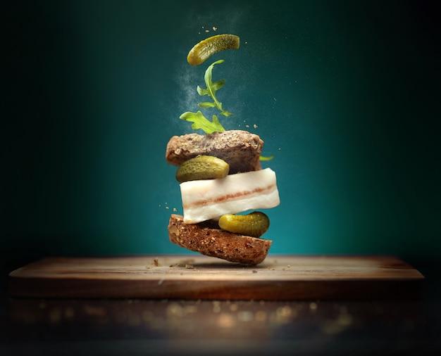 Бутерброд в народном стиле с ломтиком бекона на синем фоне с летающими ингредиентами, солеными огурцами и рукколой