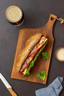 샐러드, 베이컨, 토마토 및 치즈와 함께 어두운 빵 샌드위치. 아침밥. 패스트 푸드.