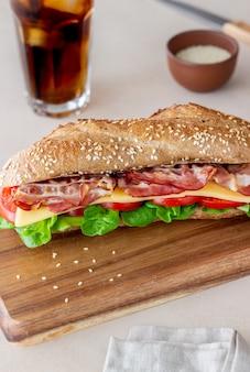 Бутерброд из темного хлеба с салатом, беконом, помидорами и сыром. завтрак. быстрое питание.