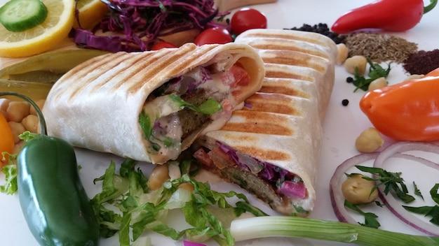 ビーフチーズとレタスをスライスしたサンドイッチは、チェリートマトのプレートの上にあります