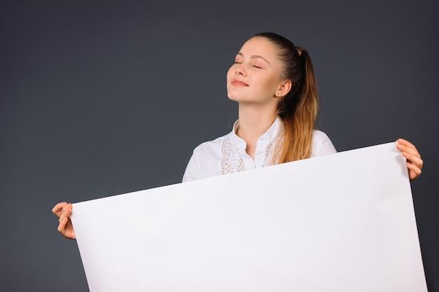 만족 된 젊은 비즈니스 우먼 그녀의 손에 빈 흰색 배너를 보유