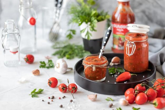 Соус из свежих красных помидоров в стеклянной банке на черной тарелке. веточка свежих помидоров черри, чеснок, острый перец, укроп и петрушка на белом столе. банка домашнего кетчупа.