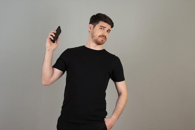 Испуганный молодой парень держит телефон на сером.