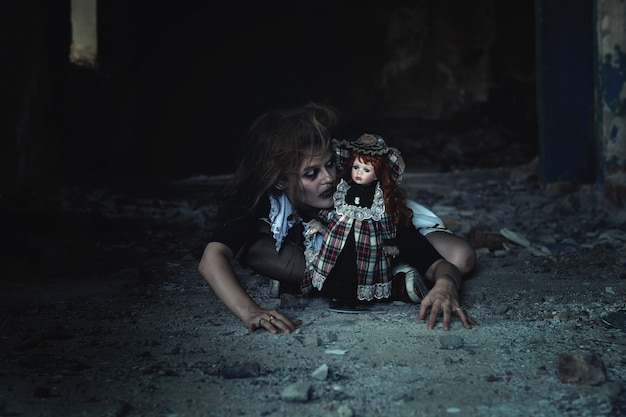 Страшная девочка с куклой на полу в заброшенном доме. идея на хэллоуин
