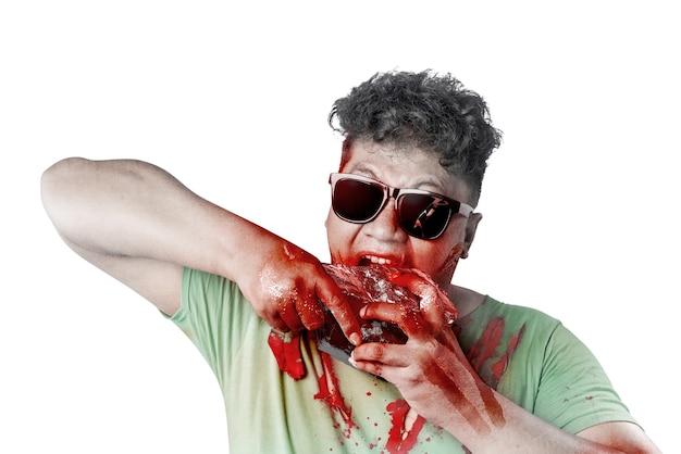 彼の体に血と傷を持つサングラスの怖いゾンビは、白い背景の上に分離された生肉を食べる