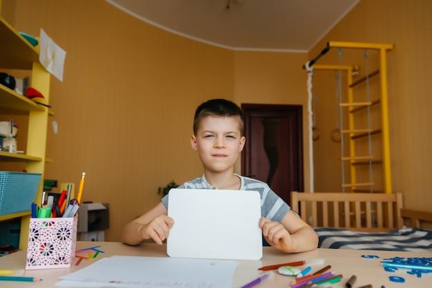 学齢期の少年は家で宿題をします。学校でのトレーニング