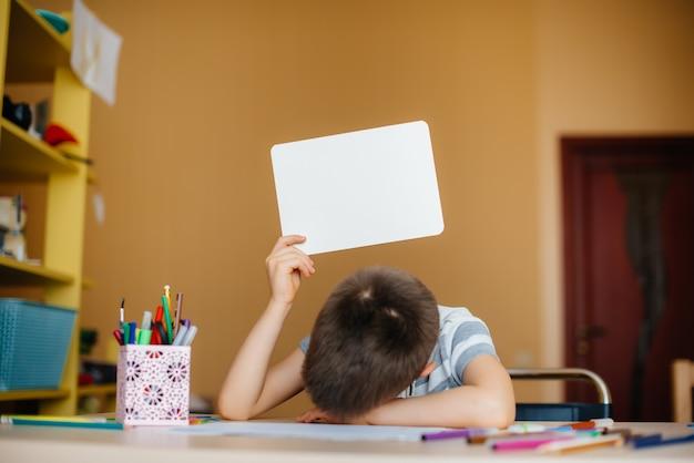 Мальчик школьного возраста делает домашнее задание дома. обучение в школе.