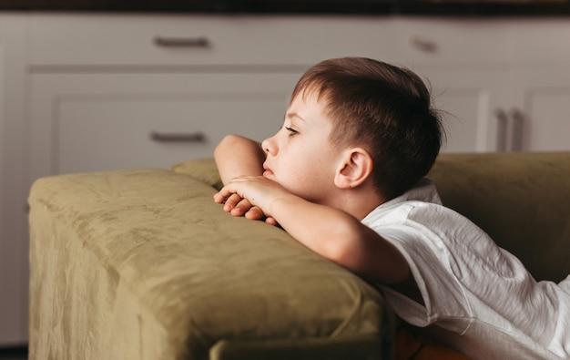집에서 소파에 누워 지루함을 느끼는 학령기 소년, 사회적 거리두기, 격리, 격리. 개념을 잠급니다. 정신 건강