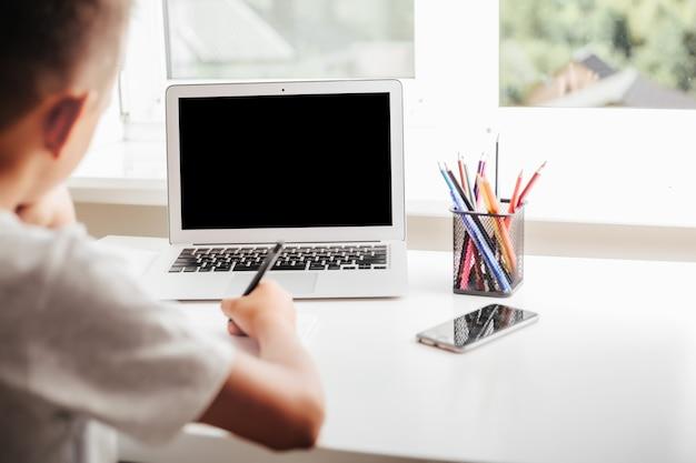 オンラインホームスクーリングを通じて自宅で学校。子供はコンピューターに座っています