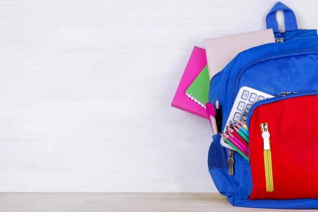 白い木製の背景に学用品の学校のバックパック