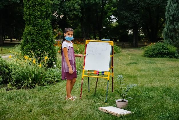 Школьница в маске стоит и пишет уроки на доске. снова в школу, учусь во время пандемии.