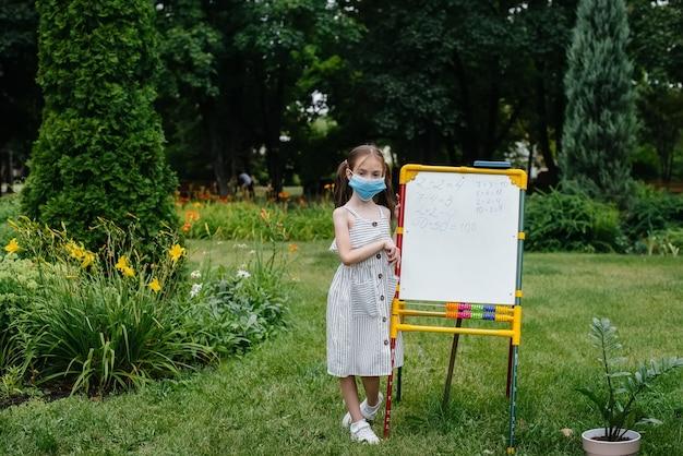 マスクをした女子校生が立って黒板にレッスンを書く