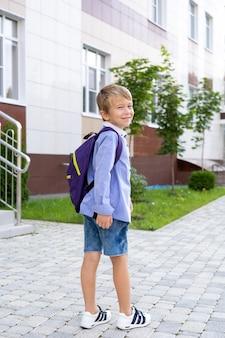 Школьник стоит с рюкзаком возле школы, начальной школы
