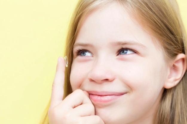 男子生徒の女の子がコンタクトレンズを目に挿入します。