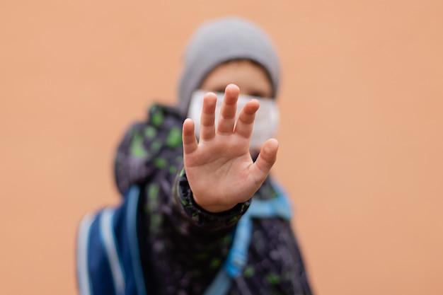 보호 마스크를 쓴 남학생이 손을 보여줍니다.