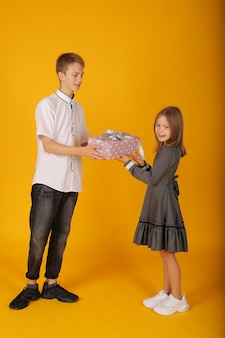 Школьник в белой рубашке и серых брюках дарит подарочную коробку школьнице сестре
