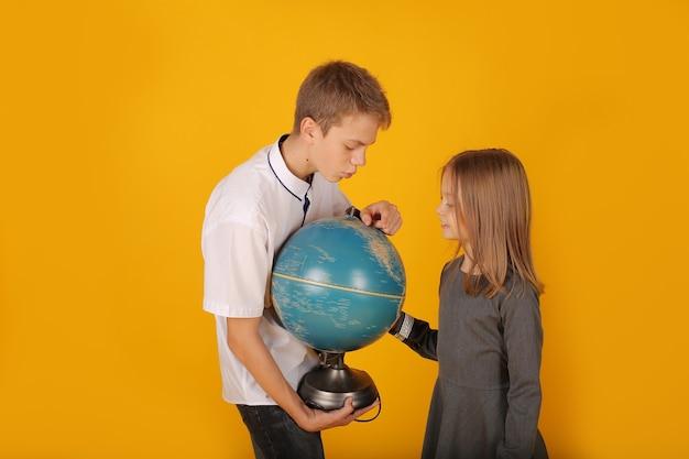 Школьник в белой рубашке и серых брюках смотрит на глобус со школьницей-сестрой