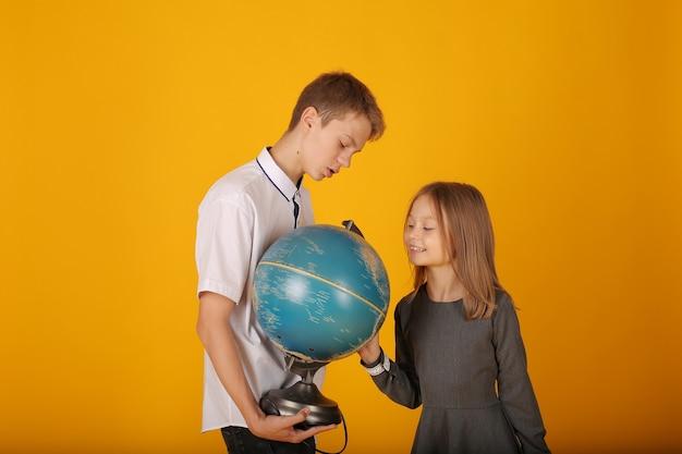 Школьник в белой рубашке и серых брюках смотрит на глобус со школьницей-сестрой Premium Фотографии