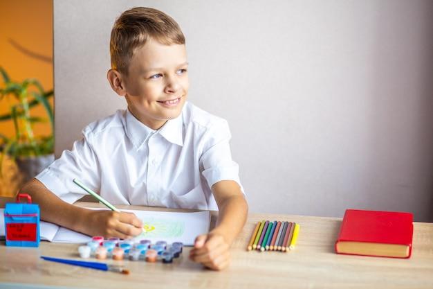 흰색 셔츠를 입은 남학생은 페인트 배경에 연필로 앨범을 그립니다.