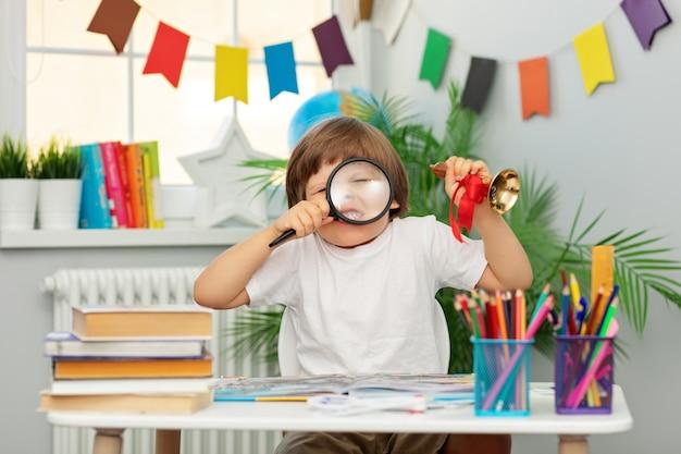 Школьник в белой футболке сидит за партой, держа в руках увеличительное стекло и колокольчик с красной лентой